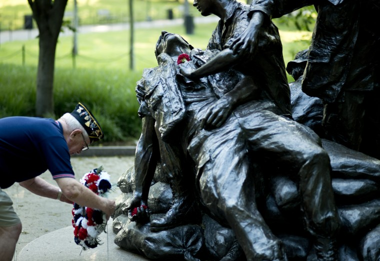 Richard Evans of the American Legion Post 24 places a wreath at a memorial to the nurses who served in Vietnam May 28, 2012 at the Vietnam Memorial in Washington, DC. (Brendan Smialowski/AFP/Getty Images)