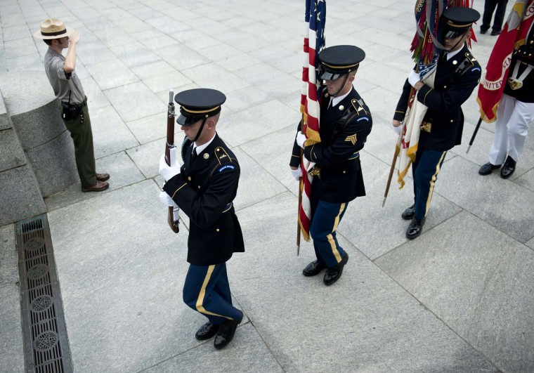 A U.S. Military color guard advances the colors as a U.S. Park ranger salutes during a wreath laying ceremony at the World War II Memorial on May 28, 2012 in Washington, DC. (Brendan SmialowskiAFP/Getty Images)