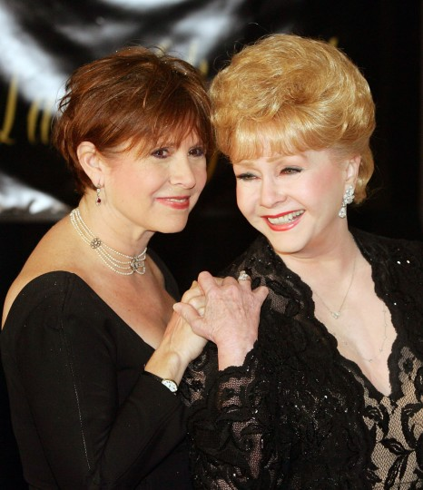 Debbie Reynolds (R) had been a darling in the public eye years before Carrie Fisher (L) was an apple in hers. As Carrie grew to grab her own piece of stardom, she remained open about growing up in a fame-soaked and scandal-riddled family. Pictured: Actress Carrie Fisher and her mother, actress Debbie Reynolds, arrive for Dame Elizabeth Taylor's 75th birthday party at the Ritz-Carlton, Lake Las Vegas on February 27, 2007. (Ethan Miller/Getty Images)