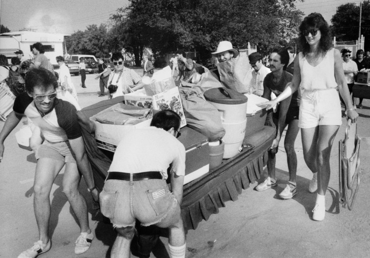 Race goers carry old sofa loaded with drinks and food as gates to the infield open at the Pimlico Race Track for the 1986 Preakness Stakes. (George Cook/Baltimore Sun)