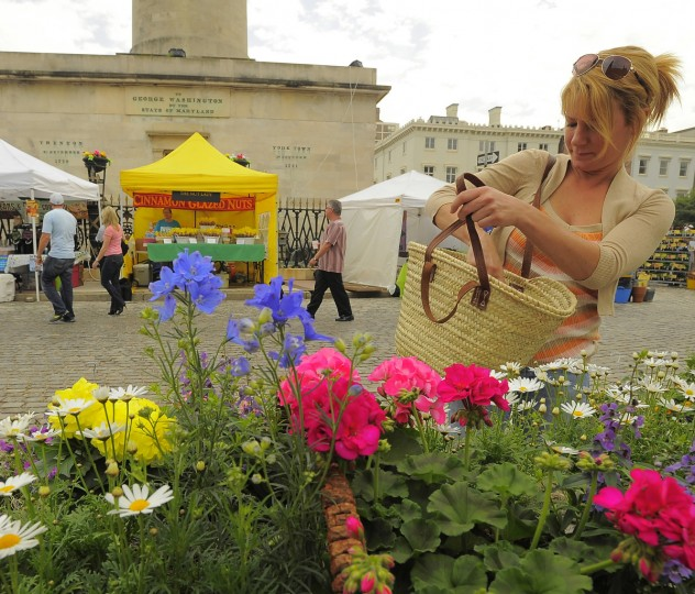 Zorana Grdjic of Fells Point makes a purchase at Baltimore's FlowerMart 2012 in Mount Vernon on Friday. (Karl Merton Ferron / Baltimore Sun Staff)