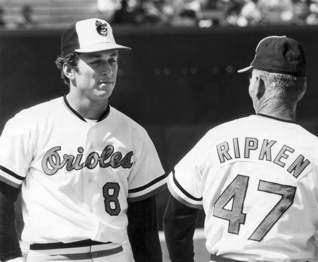 The Ripkens, Cal, Jr., left, and his dad, Oriole coach Cal, Sr., get together for a little chat before the young Oriole third baseman made his first Opening Day start. Young Cal homered in his first time at bat. (Joseph A. DiPaola/Baltimore Sun)