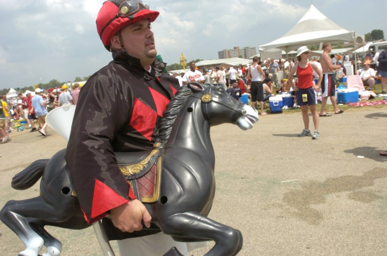 Mike DeCarlo of Phildelphia, carries a horse beer bong into the infield in 2004. (Christopher T. Assaf/Baltimore Sun)