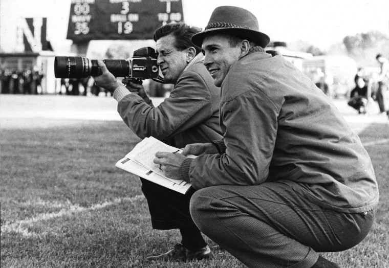 Baltimore Sun photographer Joseph A DiPaolo, Jr, left, shoots a picture during a Navy practice. Assisting him by taking captions is Orioles third baseman, Brooks Robinson, who has been following the Navy football team and their quarterback, Roger Staubach durng the Orioles' 1963 off season. (Baltimore Sun file photo)