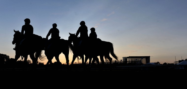 Riders walk their horses on the track during Friday morning workouts at Pimlico Race Course. (Kim Hairston/Baltimore Sun)