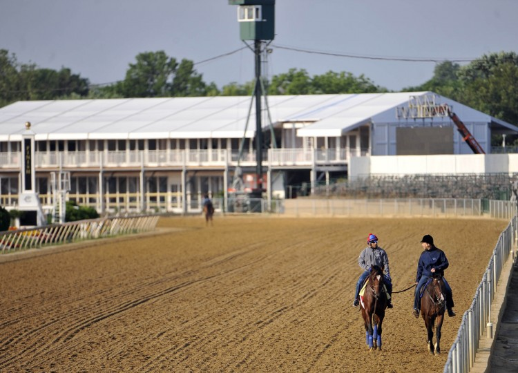 Exercise rider Zeke Castro (left) on Went the Day Well talks with trainer Graham Motion as they walk the track at Pimlico Race Course following a morning exercise session. (Kim Hairston/Baltimore Sun)