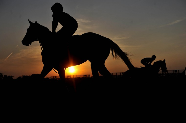 Riders and horses workout on the track as the sun rises over Pimlico Race Course Thursday morning. (Kim Hairston/Baltimore Sun)