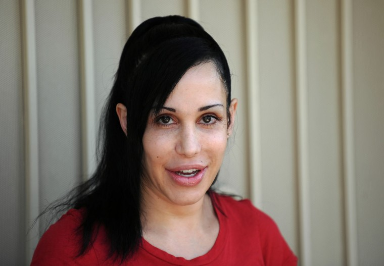 """Octomom"" Nadya Suleman faced possible home foreclosure and agreed to display a banner for Peta who offered to give her $5,000 USD and a month's worth of free veggie dogs and veggie burgers. Pictured: Suleman poses for photographers in front of her home in La Habra, California on May 19, 2010. (Gabriel Bouys/AFP/Getty Images)"