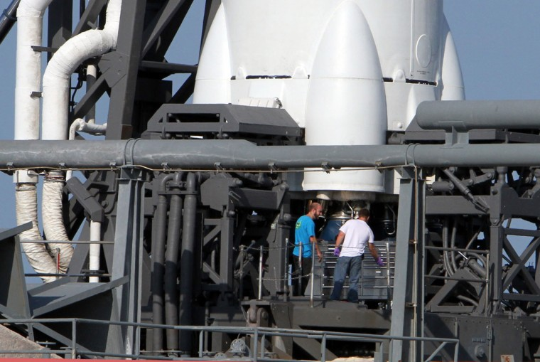 May 19, 2012: SpaceX workers gather at the Falcon 9 rocket engines after and attempt to launch its Falcon 9 rocket was aborted at Cape Canaveral, Florida. (Red Huber/Orlando Sentinel/MCT)