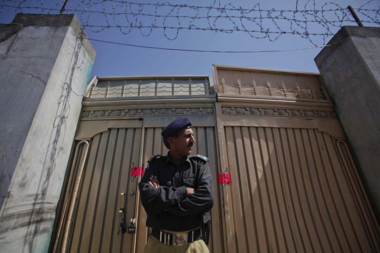 A policeman stands guard outside one of two gates of the compound where al-Qaida leader Osama bin Laden was killed. Bin Laden lived in the compound for 5-6 years before his death in May 2011. (Akhtar Soomro/Reuters)