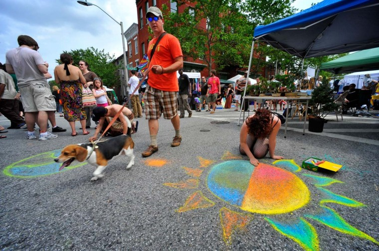 "Derek Hunt walks through the 2009 Sowebohemian Arts and Music Festival with his beagle, Leia. Also pictured are chalk artists Joshua ""Jonas"" Becker (left) and Shaina Craft (right). (Amy Davis/Baltimore Sun, May 24, 2009."
