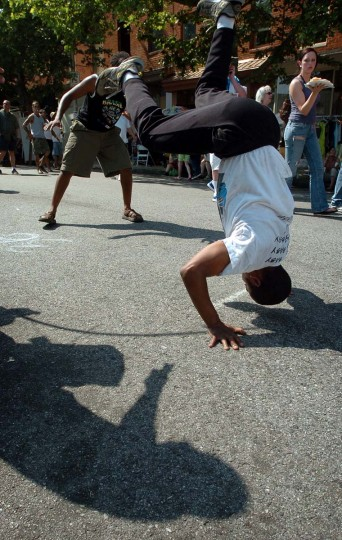 Jason Harris (center) dances capoeira-style with Pirata (left) at the 2006 Sowebohemian Arts and Music Festival. In the foreground is the shadow of Marcos DeAlencar playing the drum. (Kenneth K. Lam/Baltimore Sun, May 28, 2006).
