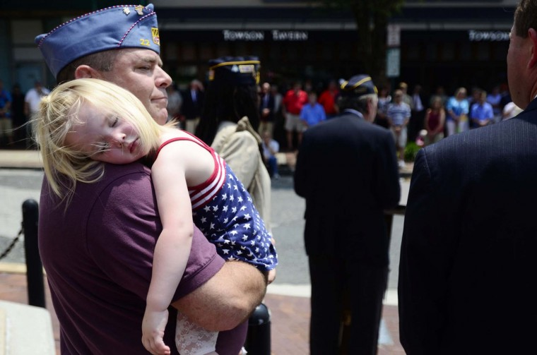 Stu Crook, commander of the Towson American Legion, holds his sleeping granddaughter Kaylee Owens, 3, at the Memorial Day services at the Wayside Cross in Towson on Sunday, May 27th. (Noah Scialom)
