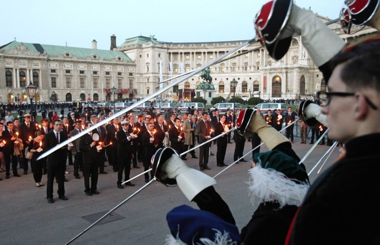 May 8, 2012: Members of traditional Austrian fraternities hold torches and raise their swords during a commemoration ceremony for the victims of World War II in front of Hofburg palace in Vienna. (Heinz-Peter Bader/Reuters)