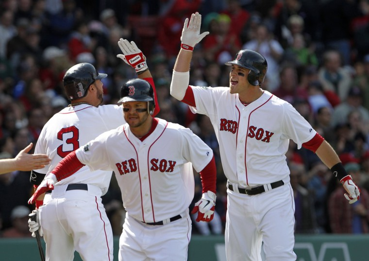 Boston Red Sox's Mike Aviles, left, congratulates Will Middlebrooks, right, on his grand slam against the Baltimore Orioles as Red Sox's Cody Ross runs back to the dugout during the fifth inning of American League MLB baseball action at Fenway Park in Boston. (Jessica Rinaldi/Reuters photo)