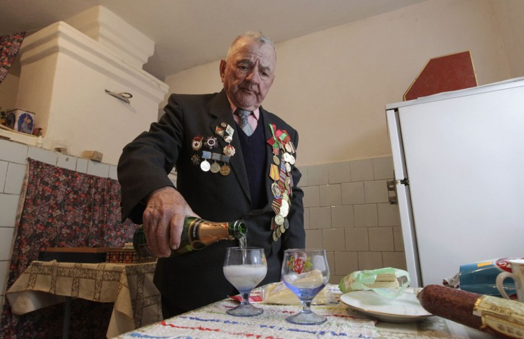 May 8, 2012:World War Two veteran Adam Aliferovich, 87, fills up glasses with champagne in his house on the eve of Victory Day in the town of Zhitkovichi, some 270 km (167 miles) south of Minsk. (Vasily Fedosenko/Retures)