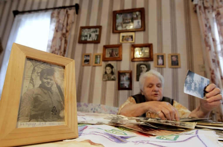 May 8, 2012: World War Two veteran Anna Beliai, 86, looks at photographs in her house in the town of Turov, some 270 km (167 miles) south of Minsk, Belarus. (Vasily Fedosenko/Retures)