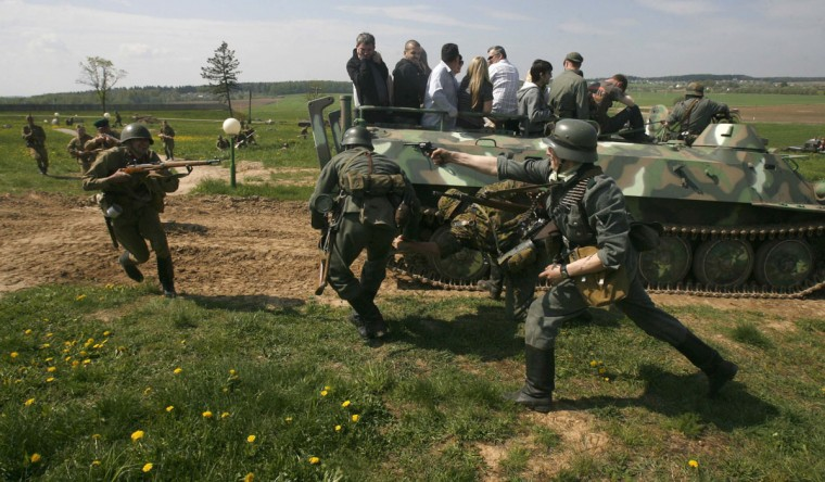 """May 6, 2012: Spectators watch from a roofless armoured vehicle as military enthusiasts take part in a re-enactment of a World War II battle at the """"Stalin Line"""" memorial, near the village of Goroshki, about 30 km (19 miles) west of Minsk, Belarus. (Vladimir Nikolsky/Reuters)"""