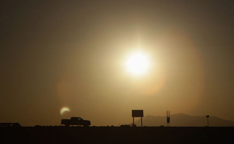 A partial eclipse is seen from a camera reflection behind a pickup near Flagstaff, Arizona. (Jason Lee/Reuters)