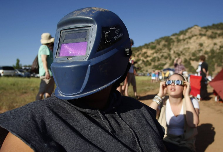 "Amaleah Barker wears a welding mask as a rare annular eclipse dims the sky, as the sun and moon align for ""ring of fire"" spectacle over the southwestern town of Kanarraville, Utah. Eclipses of some type occur almost every year, but stargazers have not seen an annular - shaped like a ring - eclipse on U.S. soil since 1994, and the next one is not to occur until 2023. (Jim Urquhart/Reuters)"