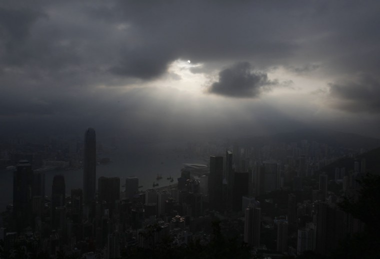 The moon passes between the sun and the earth over Hong Kong's Victoria Harbour during a solar eclipse seen from the Peak on Hong Kong Island May 21, 2012. (Bobby Yip/Reuters)