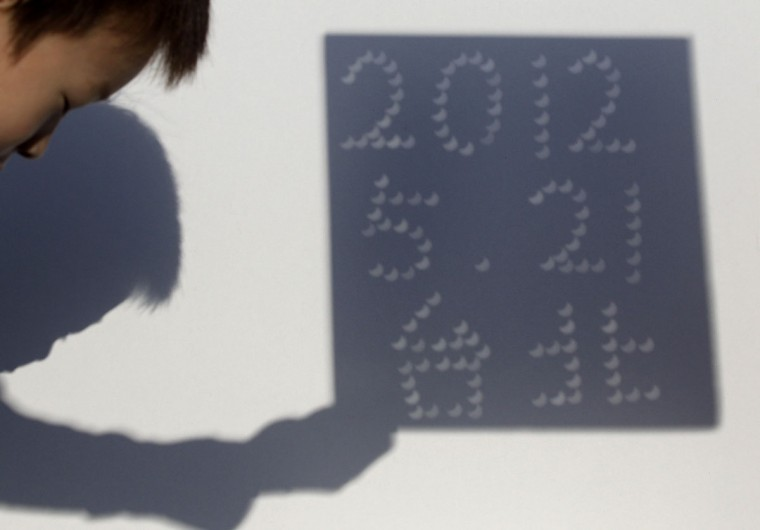 "A child looks at projections produced during an eclipse at Taipei Astronomical Museum May 21, 2012. The Chinese characters read, ""Taipei."" (Pichi Chuang/Reuters)"