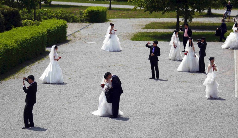 The couples take pictures after their wedding in Fuessen, Germany.(Michael Dalder/Reuters photo)