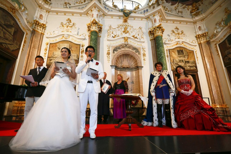 Chinese bridal couples give a speech after their symbolic wedding, Germany. (Michael Dalder/Reuters photo)