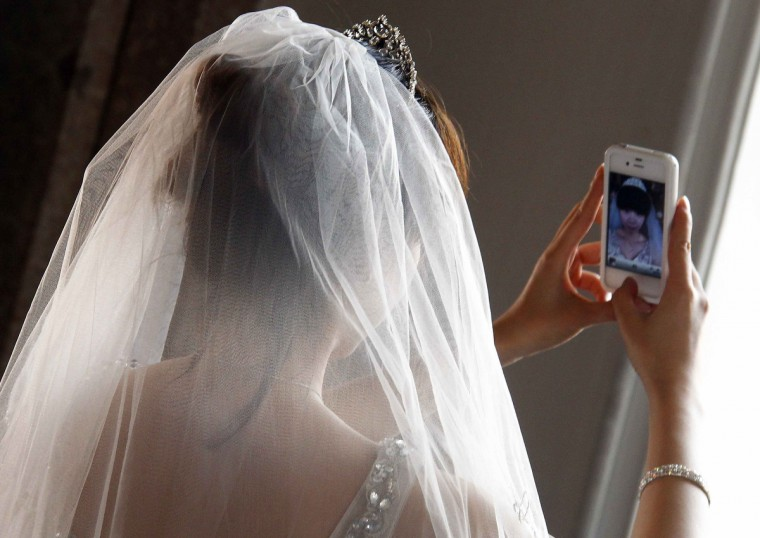 A Chinese bride takes a self-portrait before her symbolic wedding. (Michael Dalder/Reuters photo)