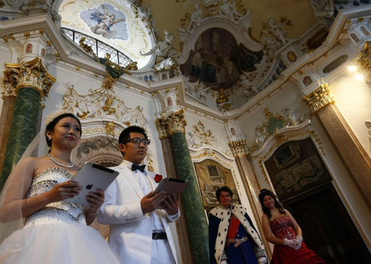Chinese bridal couples give a speech after their symbolic wedding in Fuessen. (Michael Dalder/Reuters photo)