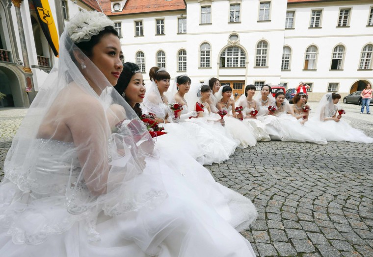 Chinese brides pose after their symbolic wedding in Fuessen. 15 Chinese couples who already got married in China, travelled to Germany to repeat their promise of marriage at Neuschwanstein Castle, one of the most popular destinations in Europe. (Michael Dalder/Reuters photo)