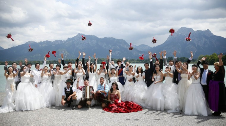 Chinese bridal couples toss their flowers after their symbolic wedding in Fuessen. (Michael Dalder/Reuters photo)