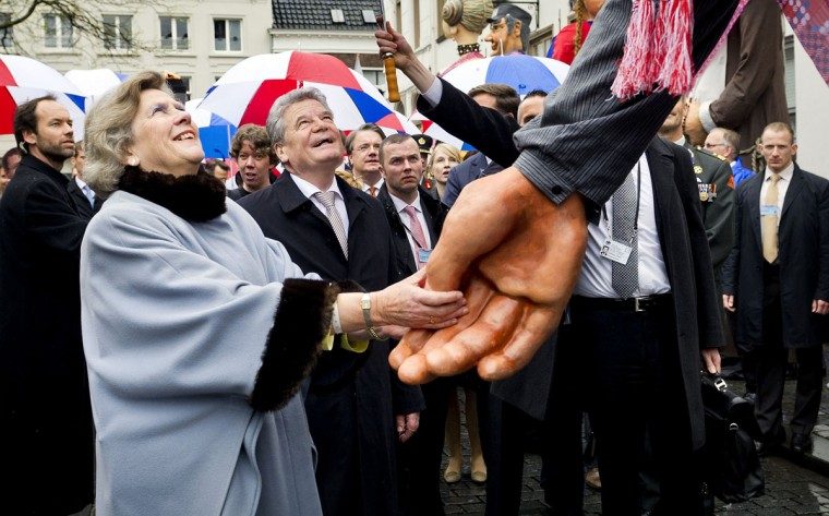 May 5, 2012: German President Joachim Gauck (3rd R) and Joan Leemhuis-Stout (2nd R), chairman of the National Liberation Day committee, shake hands with a giant puppet as they walk towards the ignition of the freedom fire on National Liberation Day at Castle Square in Breda, The Netherlands. (Koen van Weel/Pool/Reuters)