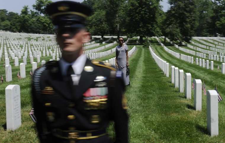 A woman looks on from the graves as a member of the honor guard stands watch at Arlington National Cemetery May 28, 2012. (Jonathan Ernst/Reuters)