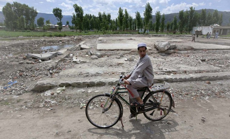 A boy cycles past the demolished site of Osama bin Laden's compound in Abbottabad May 1, 2012. (Mian Khursheed/Reuters)