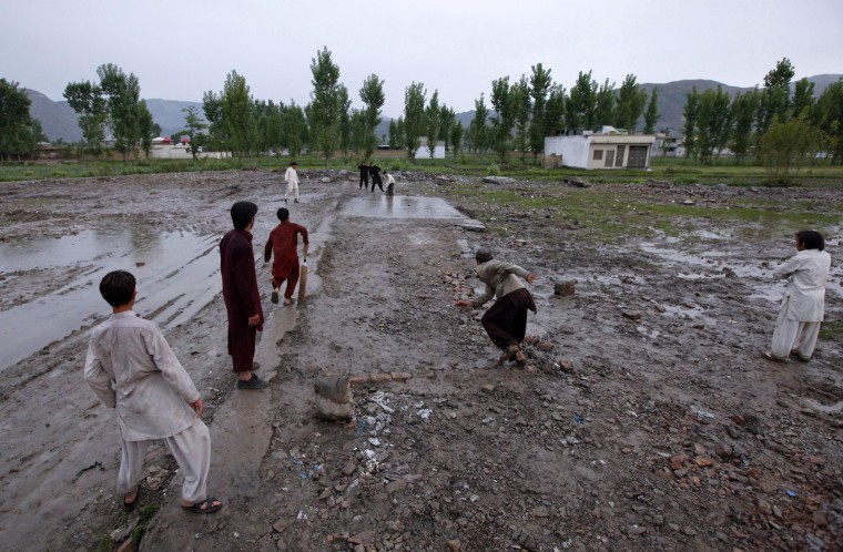 Children play cricket in the rain on the demolished site of the compound of Osama bin Laden, in Abbottabad April 20, 2012. (Akhtar Soomro/Reuters)