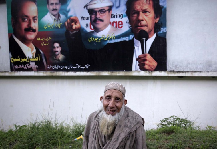 An elderly man stands in front of a political campaign billboard in Abbottabad April 22, 2012, where Osama bin Laden was killed a year ago. (Akhtar Soomro/Reuters)