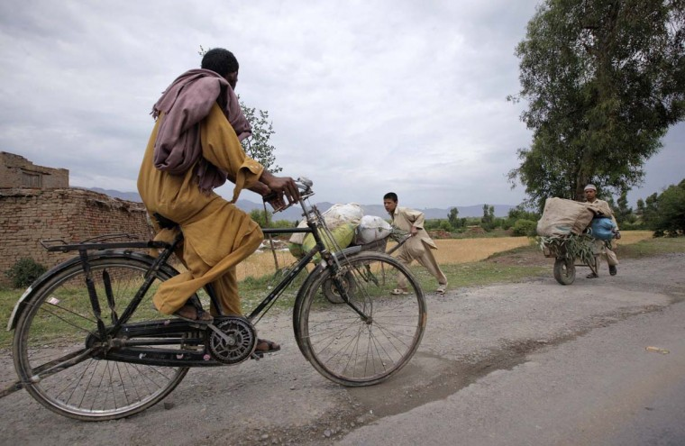 A man rides a bicycle as children push wheelbarrows along a road on the outskirts of Abbottabad April 22, 2012. (Akhtar Soomro/Reuters)