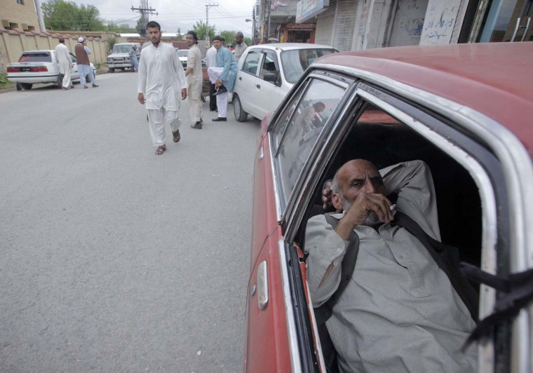 A taxi driver smokes a cigarette while he waits for passengers along a road in Abbottabad April 20, 2012. (Akhtar Soomro/Reuters)