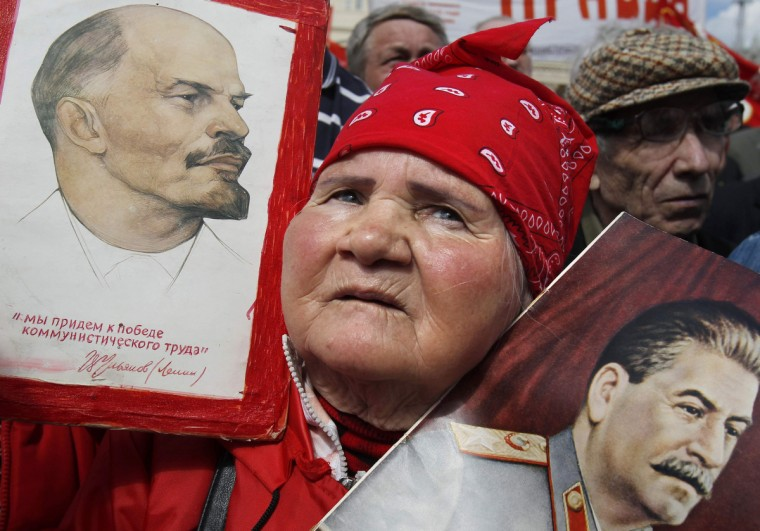 A Russian communist holds placards with portraits of Vladimir Lenin and Joseph Stalin during a rally to celebrate International Workers' Day, or Labour Day in Moscow. (Denis Sinyakov/Reuters)