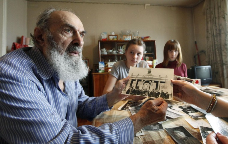 May 8, 2012: Hayyim Broy (L), a 87-year-old Jewish Red Army veteran of World War Two, holds up an old photograph during a visit by volunteer hairdressers to his apartment in Russia's Siberian city of Krasnoyarsk. As a former front scout and a soldier of the infantry, Broy fought at the 1st Belarusian Front under the command of Marshal of the Soviet Union Georgy Zhukov. He was seriously wounded during a battle in Berlin in May, 1945. (Ilya Naymushin/Reuters)