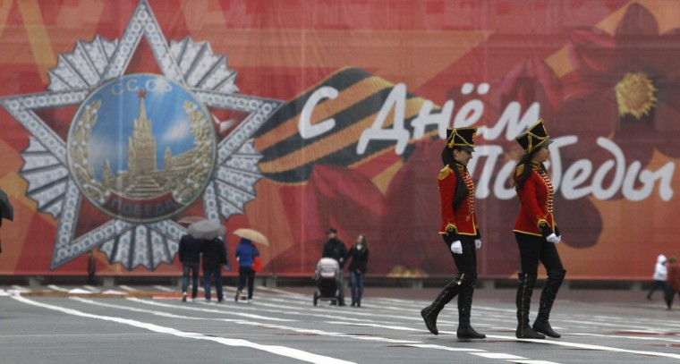 May 5, 2012: Women in historical dress walk in front of a billboard dedicated to Victory Day celebrations on Palace Square in St. Petersburg. (Alexander Demianchuk/Reuters)