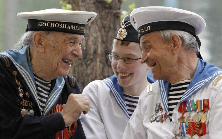 May 9, 2012: World War II veterans share a joke, as a boy wearing a navy uniform listens to them, during a Victory Day celebration in Gorky Park in Moscow. (Denis Sinyakov/Reuters)