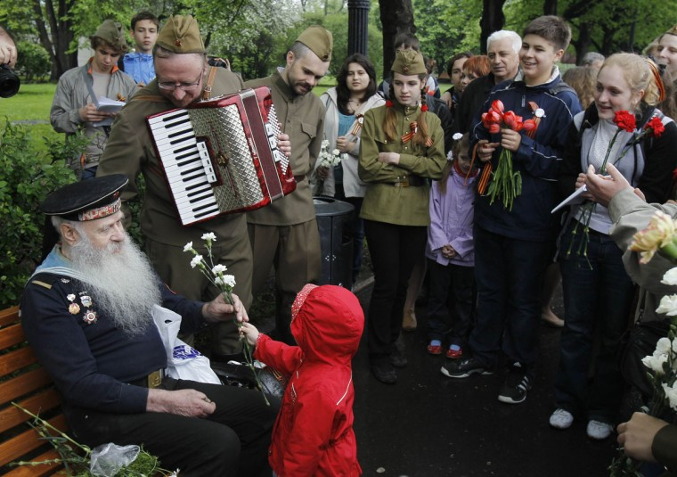 May 9, 2012: World War II veteran Fyodor Bortsov (L), 86, is offered a bunch of flowers by a child in Gorky Park during a Victory Day celebration in Moscow. (Denis Sinyakov/Reuters)