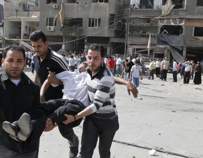 An injured man is carried after an explosion in Damascus, Syria. Two explosions shook the Syrian capital Damascus on Thursday, killing and wounding dozens of people, state media said, in a district that houses a military intelligence complex involved in President Bashar al-Assad's crackdown on a 14-month uprising. (Khaled al-Hariri/Reuters photo)