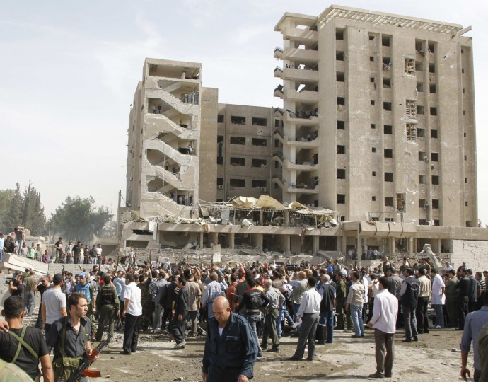 Residents and security personnel gather at the site of an explosion in Damascus. Two explosions shook the Syrian capital Damascus on Thursday. (Khaled al-Hariri/Reuters photo)