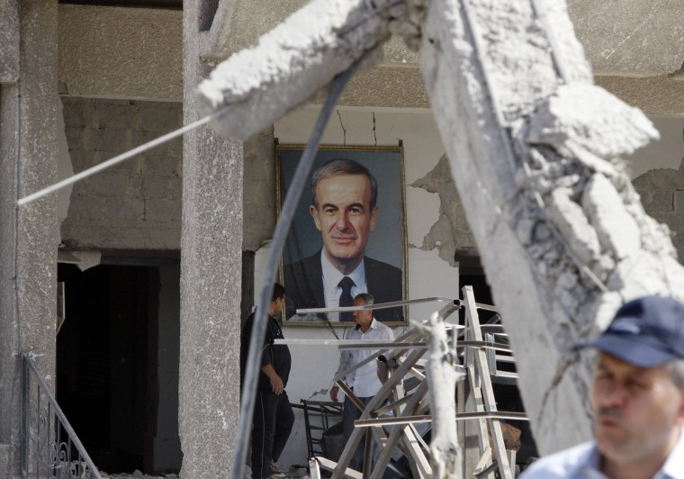A framed portrait of Syria's late President Hafez al-Assad, father of current President Bashar al-Assad, is seen at the site of an explosion in a security building in Damascus . Two large explosions killed 40 people in Damascus on Thursday, state media said, destroying dozens of cars on a highway and damaging an intelligence complex involved in President Bashar al-Assad's crackdown on a 14-month-old uprising. (Khaled al-Hariri/Reuters photo)