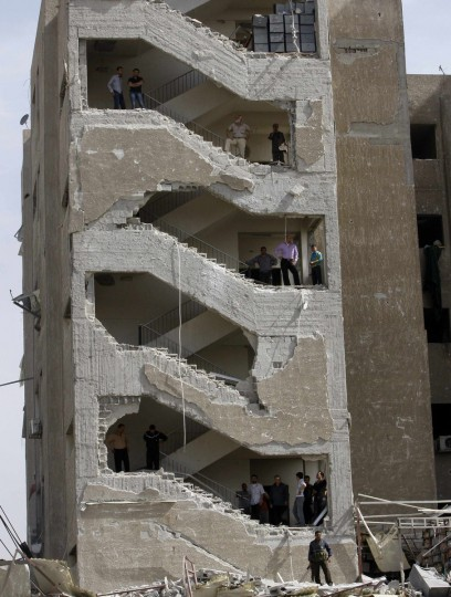 Men stand at different stair landings of an intelligence complex that was damaged during an explosion in Damascus. (Khaled al-Hariri/Reuters photo)