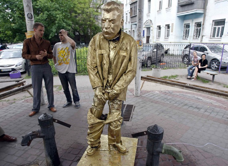 """May 7, 2012: Two men stand near a statue of Soviet dictator Josef Stalin, styled after Brussels' """"Manneken Pis"""" (Peeing Boy) and installed by members of the Bratstvo (Brotherhood) nationalist party in Kiev. Ukraine, along with other ex-Soviet republics, will celebrate the 67th anniversary of the Allied victory in the Second World War on May 9, but nationalists, who consider the Soviet era a period of Russian occupation, denounce the celebrations. (Gleb Garanich/Reuters)"""