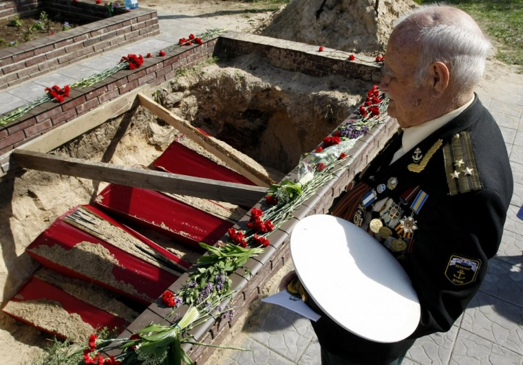 May 6, 2012: A veteran looks at coffins, containing the remains of soldiers killed in World War Two, during a reburial ceremony near the village of Petrivsk, some 70 km (43 miles) from Kiev. (Anatolii Stepanov/Reuters)